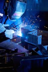 Welder welding in a manufacturing plant