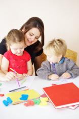 Mother or teacher helping little children learn.
