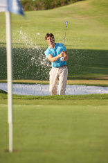 Male Golfer Playing Bunker Shot