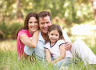 Family Sitting In Long Grass of Park