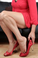 Woman legs putting on black heel shoes sitting