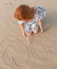 Young woman making two heart shape on the beach