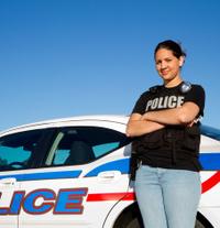 Hispanic Police woman standing against car