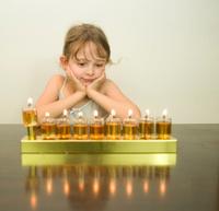 girl look at the Hanukkah menorah