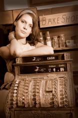 Woman behind antique cash register
