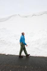Mature adult man surveys enormous snow drifts after historic sno