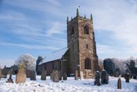 Snow on village church and graveyard
