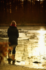 Woman stands alone by the river