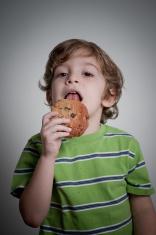 kid posing while eating cookie