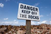 Danger Sign Near Ocean Rocks