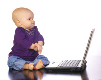 Infant Girl Looks frustrated at a laptop computer.