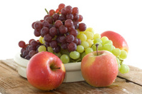 Fresh grapes and apple in a bowl