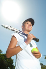 Woman smiling holding a tennis racquet