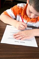 Boy in the elementary school writes math test - IV