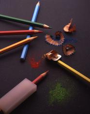 Coloured pencils pencil sharpener rubber on black backround