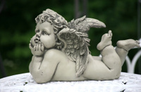 Angel figurine on iron chair in the garden