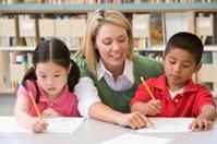 Kindergarten teacher assisting children in class