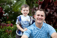 Smiling Little boy son with arm around Father outdoors