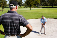 Man looking at male golfer playing his stroke