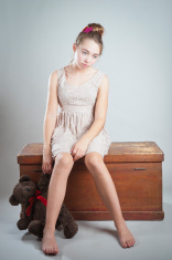 Sad young girl with teddy bear.