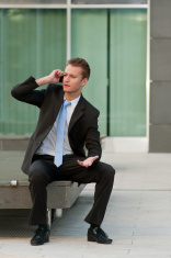 Young buisness man sitting on bench in front of office