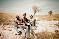 Three Africans Men Playing Djembe In The Meadow