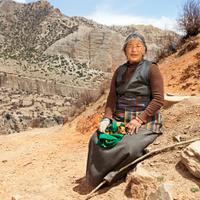 Tibetan woman sitting on the rock. Mustang, Nepal.
