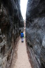 Child Hiking Narrow Trail Between Rock Walls