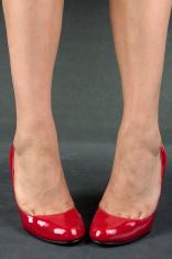 Woman feet with high heels over grey