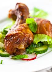 Roasted chicken legs on vegetable salad