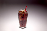 Clear glass containing ice and soda with red straw shot