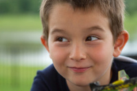 Close-up of a kid looking happily and suspiciously