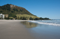 Mount Maunganui reflected in wet sand.