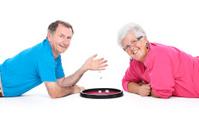 happy senior couple playing dice