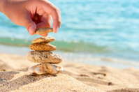 Stone tower on sand with hand against sea