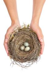 Young woman holding blackbird nest