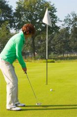 Senior golfer putting on a golf green