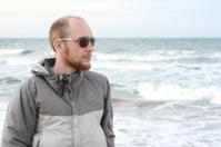 portrait of man with beard in sunglasses near sea