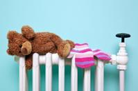 Teddy bear and gloves on an old radiator
