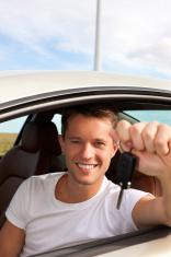 Man is holding his car key sitting inside