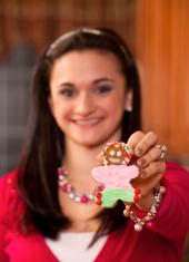 Teen Girl Displays Decorated Gingerbread Man Cookie (series)