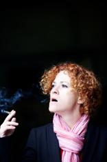 Redheaded woman smoking a cigarette