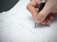 Close up of man filling a resume with pen