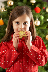 Young Girl Eating Star Shaped Christmas Cookie