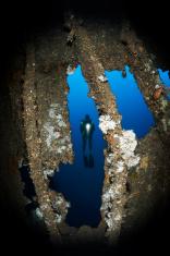 Scuba Diver Behind The Wreck