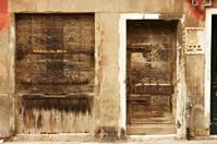 Ruined door and shutters in Venice .