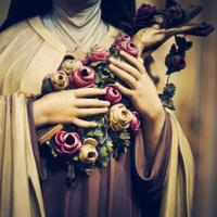 femaile saint holding a crucifix