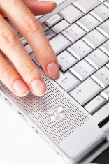 Finger pressing the enter key on laptop keyboard.