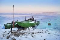 Boats on frozen lake