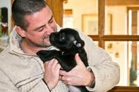 Man Cuddling Puppy